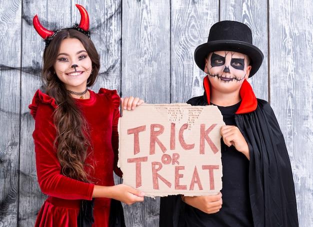 Frères tenant astuce ou traiter signe dans des costumes d'halloween