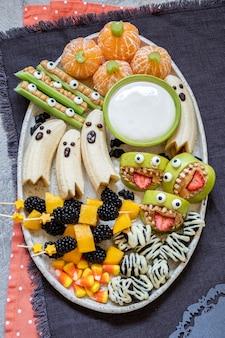 Friandises d'halloween aux fruits sains. fantômes de banane, citrouilles orange clémentine et montures monstre aux pommes