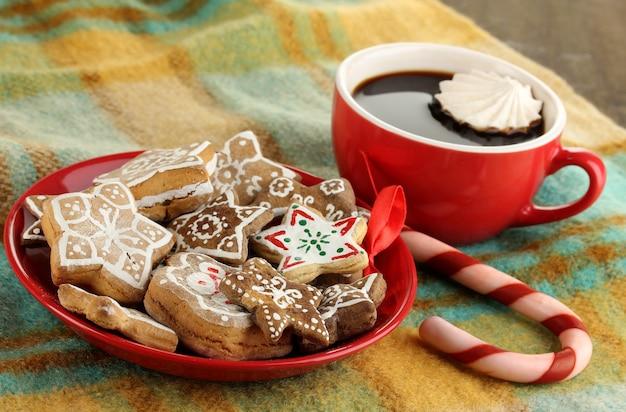 Friandises de noël sur assiette et tasse de café en gros plan à carreaux