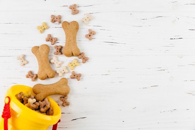Friandises pour chiens dans un seau sur une surface en bois blanche