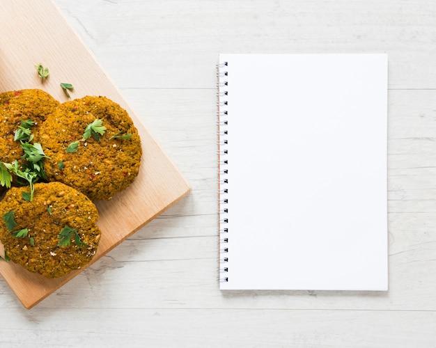 Des friandises végétaliennes à côté d'un cahier vide