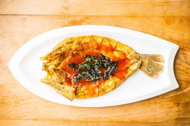 Fried poissons de loup de mer en plaque blanche avec la sauce épicée et sucrée