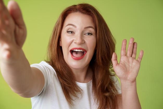 Friendly gaie rousse moyenne femme étendre le bras tenir la caméra prenant selfie en agitant la paume salut bonjour salutation souriant largement bienvenue fille parler appel vidéo mur vert internet mobile