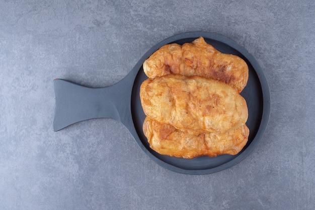Frit dans la pâte à huile dans une poêle sur une table en marbre.