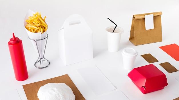 Des frites avec des aliments emballés; bouteille de sauce et tasse d'élimination sur fond blanc