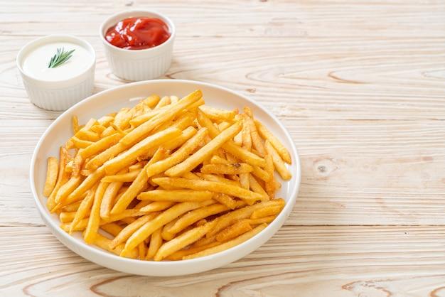 Frites ou chips de pomme de terre avec crème sure et ketchup