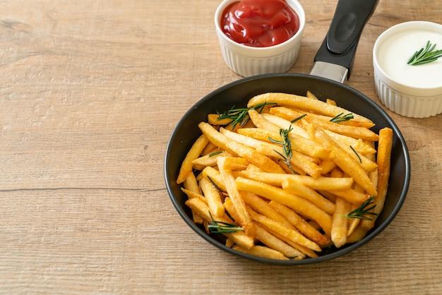 Frites ou chips de pommes de terre avec crème sure et ketchup