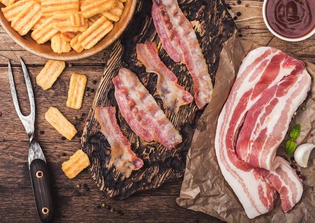 Frites de collations au bacon avec des tranches de bacon grillées sur une planche à découper vintage avec du bacon cru fumé sur du papier de boucherie à l'ail et à la sauce