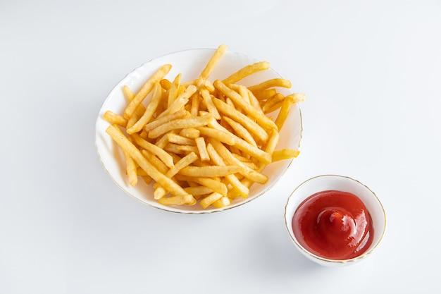 Frites croustillantes dans une assiette sur fond blanc. restauration rapide américaine chaude.