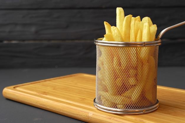 Frites dans un bol en métal sur une surface noire
