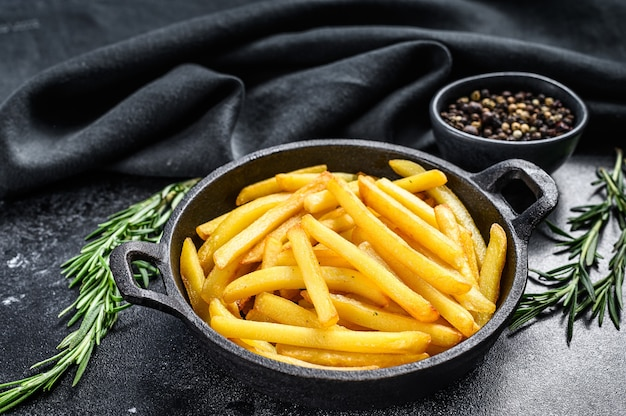 Frites dans une poêle sur fond sombre