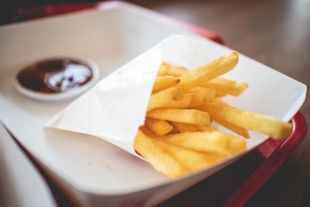 Frites dans le sac en papier avec sauce tomate servies dans le café franchisé.