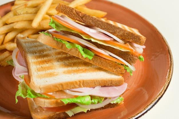 Frites et deux sandwichs avec du fromage, des saucisses et des feuilles de laitue dans une assiette grunge.