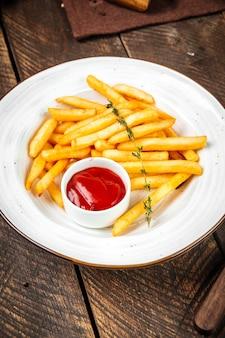 Frites avec du ketchup sur une plaque blanche sur la table en bois