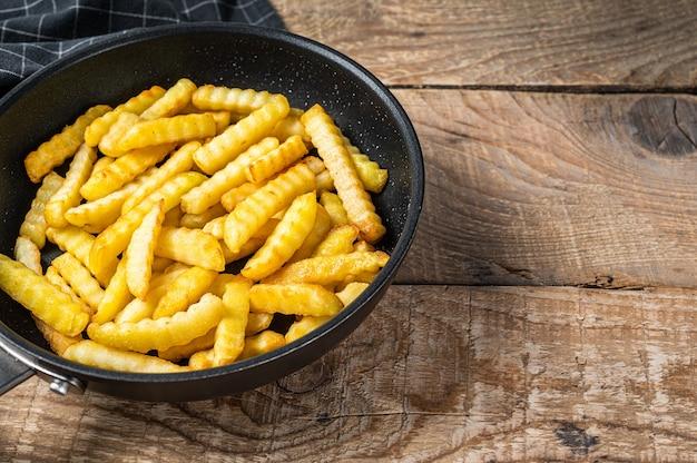Frites frites au four frites bâtonnets de pommes de terre dans une casserole. fond en bois. vue de dessus. copiez l'espace.