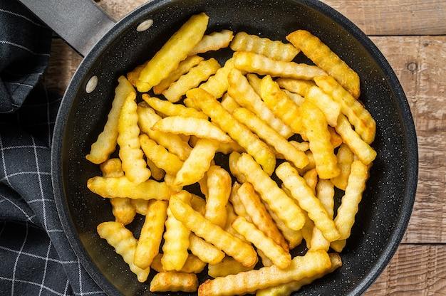 Frites frites au four frites bâtonnets de pommes de terre dans une casserole. fond en bois. vue de dessus.