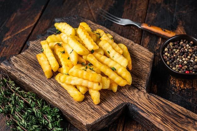Frites frites cuites au four bâtonnets ou chips sur une planche de bois. fond en bois foncé. vue de dessus.