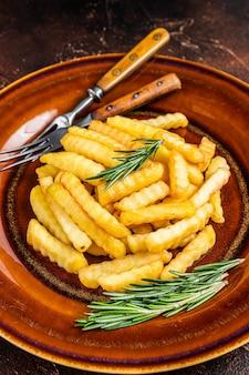 Frites frites frites ou frites dans une assiette rustique. fond sombre. vue de dessus.