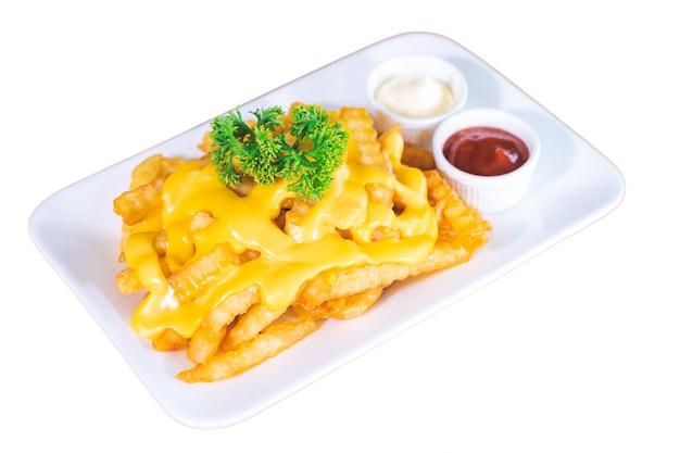 Frites garnies de fromage, servies avec sauce tomate et mayonnaise sur une plaque blanche, fond blanc isolé.