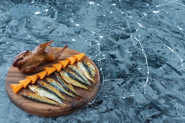Frites, grillades de poulet et de poisson sur une planche, sur la table en marbre.
