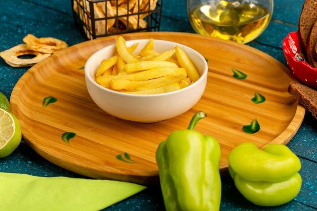 Frites à l'intérieur de la plaque avec de l'huile de poivrons verts sur bleu