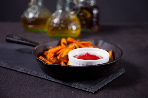 Des frites de patates douces cuites au four en bonne santé sur la poêle en métal avec une sauce tomates.
