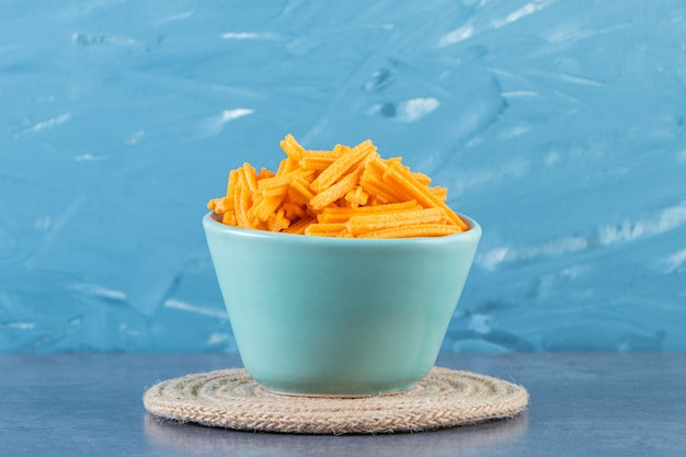 Frites de patates douces dans un bol sur un dessous de plat sur la surface en marbre