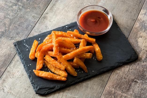 Frites de patates douces et sauce ketchup sur table en bois