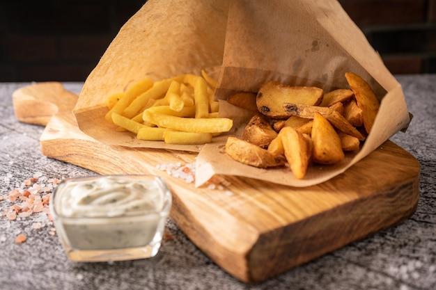 Frites sur une planche de bois avec de grandes épices et sauce naturelle sur fond sombre pour la publicité...