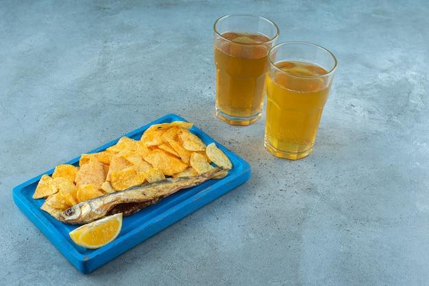 Frites et poisson sur une assiette en bois à côté de deux verres de bières , sur la table en marbre.