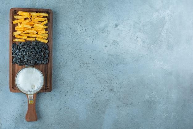 Frites de pommes de terre, graines de tournesol et un verre de bière sur une planche, sur le fond bleu.