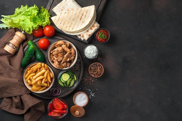 Frites, poulet frit, légumes et pain pita sur un mur marron avec espace pour copier. ingrédients pour shawarma, burritos, gyroscopes.