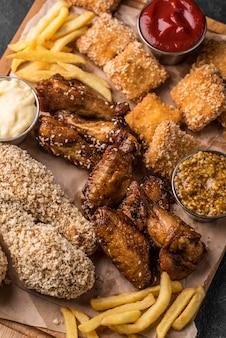 Frites et poulet frit avec des sauces sur planche à découper