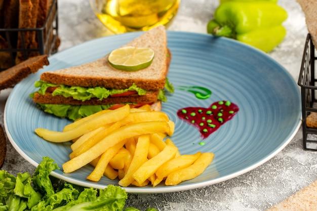 Frites avec sandwiches à l'intérieur de la plaque bleue avec de l'huile de salade verte et poivron