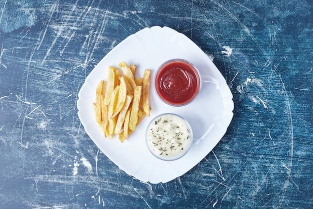 Frites avec des sauces dans une assiette blanche.