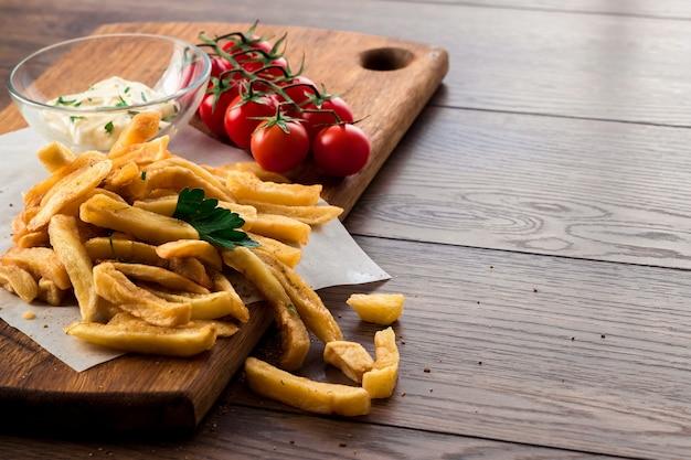 Frites, tomates cerises, sauce à l'ail sur bois