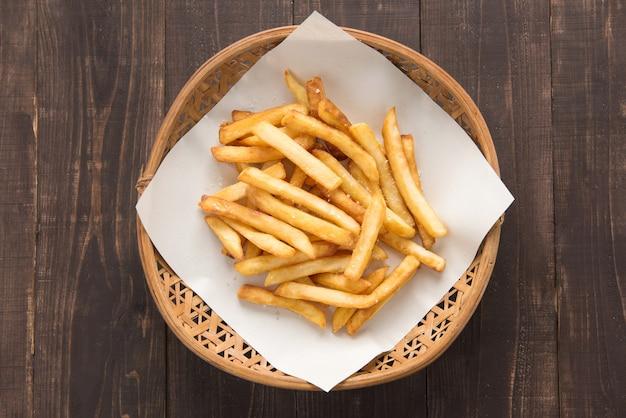 Frites traditionnelles françaises dans le panier sur fond de bois