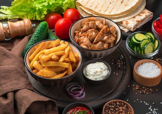 Frites, viande frite, pain pita, légumes et épices sur un mur sombre. un repas complet ou des ingrédients pour shawarma, burrito, gyros. fermer.