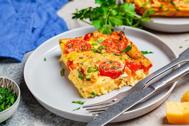 Frittata aux œufs traditionnelle (omelette) avec tomates et fromage en plaque grise.