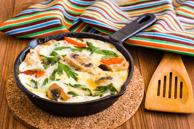 Frittata à base d'œufs, de poulet, de champignons, d'oignons, de tomates, de fromage et de persil dans une poêle en fer