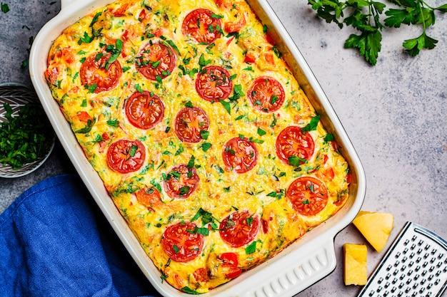 Frittata traditionnelle aux œufs avec des tomates et du fromage dans le plat de four, vue de dessus. omelette au four avec légumes et fromage.
