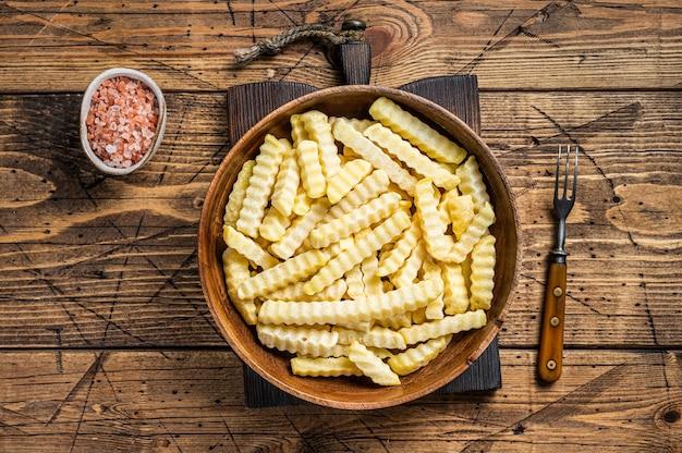 Froid frozen crinkle four frites bâtonnets de pommes de terre dans une assiette en bois