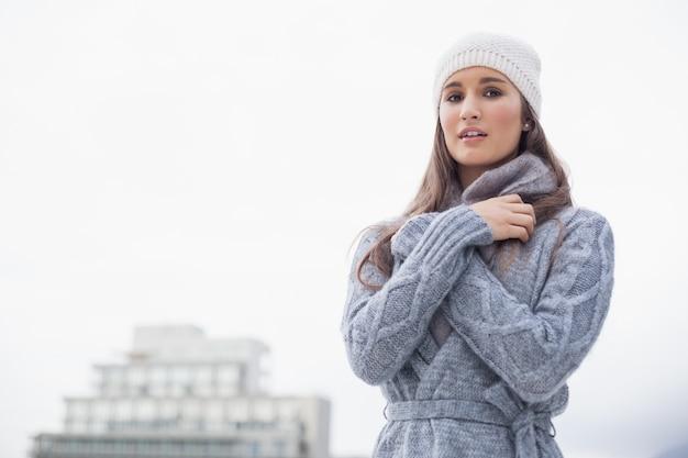 Froide jeune femme avec des vêtements d'hiver sur posant