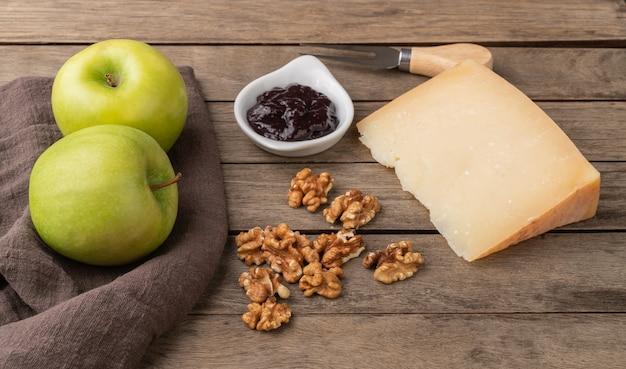 Fromage artisanal canastra du brésil sur planche de bois avec noix, confiture et pommes vertes.
