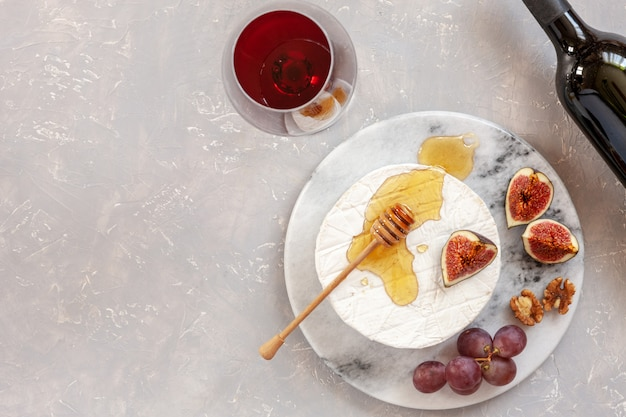 Fromage au brie doux frais avec du miel, des noix, des figues, des raisins et un verre de vin rouge.