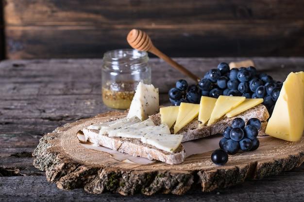 Fromage aux raisins, pain, miel. fromage de chèvre aux herbes. planche de bois naturelle.
