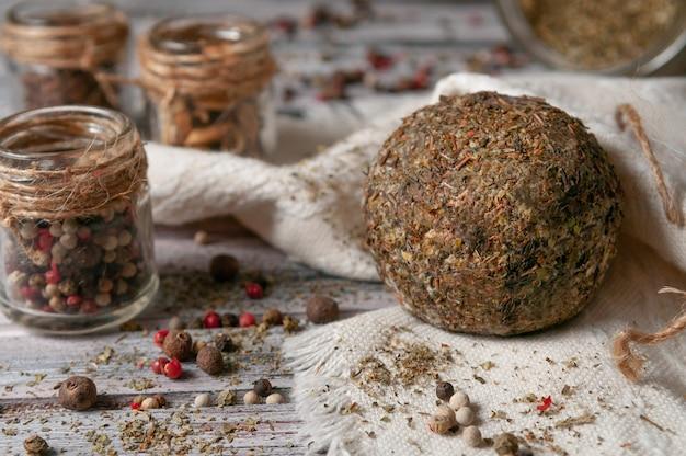 Fromage belper knolle au poivre noir et aux épices. sur une serviette textile. fond en bois gris. fermer. dans les boîtes de fond avec des épices.