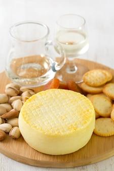 Fromage avec des biscuits, des noix et du vin sur un plateau blanc