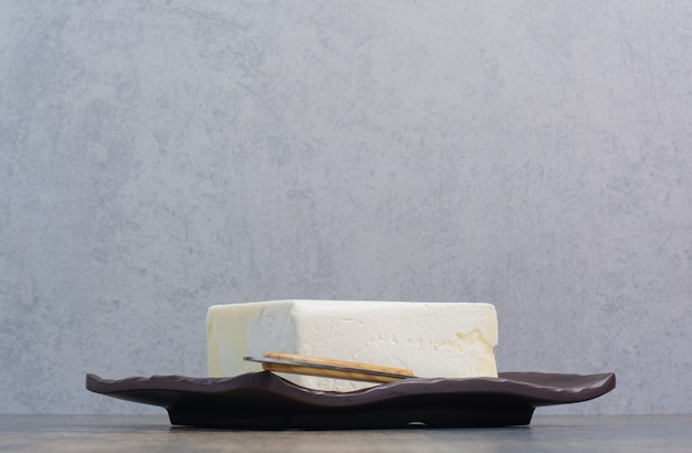 Fromage blanc sur plaque noire avec couteau