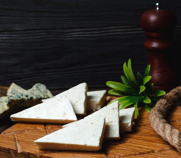 Fromage blanc triangulé sur une planche de bois